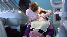 Een jonge vrouw kwam aan de tandarts voor tandbehandeling stock footage
