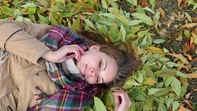 Een jonge vrouw in een laag die op de herfst liggen gaat weg Gelukkig het glimlachen stock videobeelden