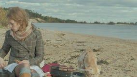 Een jonge vrouw in een laag zit op het strand door de rivier, oceaan, heeft een picknick, kookt vlees op de grill, zit een hond stock videobeelden