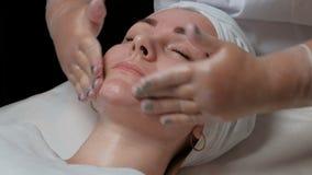 Een jonge vrouw ligt met haar die ogen tijdens een huid het reinigen procedure worden gesloten in een medische schoonheidssalon C stock footage