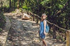 Een jonge vrouw loopt langs een bosweg stock fotografie