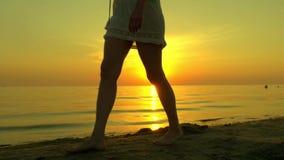 Een jonge vrouw loopt langs een zandig overzees strand blootvoets op een zonsondergangachtergrond Het meisje loopt in langzame mo stock footage