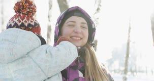 Een jonge vrouw loopt met een kind in zonnig, koud weer stock video