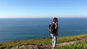 Een jonge vrouw loopt vanaf de camera op een heuvel De oceaan op een achtergrond stock videobeelden