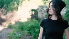Een jonge vrouw loopt voorzichtig en kijkt rond met vrees stock videobeelden
