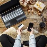 Een jonge vrouw maakt aankopen met een smartphone en een creditcard Online Winkelend De giften van Kerstmis royalty-vrije stock afbeelding