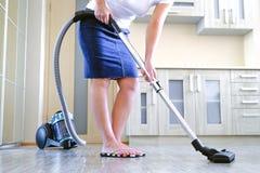 Een jonge vrouw maakt de flat schoon In de handen van een huishoudapparaat, stofzuiger Het concept netheid en royalty-vrije stock foto's