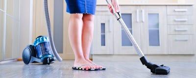 Een jonge vrouw maakt de flat schoon In de handen van een huishoudapparaat, stofzuiger Het concept netheid en royalty-vrije stock fotografie
