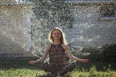 Een jonge vrouw mediteert onder de nevel van water royalty-vrije stock afbeeldingen