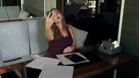 Een jonge vrouw met bovenmatig gewicht zit in een koffie en selfie stock videobeelden