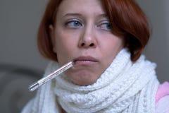 Een vrouw met een thermometer stock foto