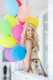 Een jonge vrouw met grote kleurrijke latexballons Stock Afbeelding