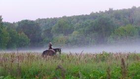 Een jonge vrouw met lang die haar en een GLB loopt over het gebied in de mist, door een jonge man wordt gevolgd die ook a berijdt stock footage