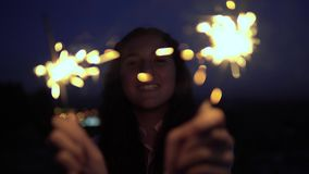 Een jonge vrouw met lang donker haar houdt vuurwerk bij nacht op de achtergrond van de stad en is gelukkig om een goed te hebben stock videobeelden