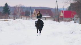 Een jonge vrouw met lang haar die een paard in een dorp berijden Achter mening stock footage