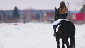 Een jonge vrouw met lang haar die een paard in een dorp berijden Status op sneeuwgrond stock video