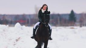 Een jonge vrouw met lang haar en rode lippenstift die een paard in een dorp berijden stock videobeelden