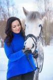 Een jonge vrouw met een mooi de winter wit paard stock foto's