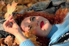 Een jonge vrouw met rood haar ligt op een deken en bekijkt een geel blad van een esdoorn Van de bladdalingen mooi s royalty-vrije stock afbeeldingen