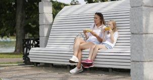 Een jonge vrouw met een rust van het blondemeisje in het park en eet heet graan stock video