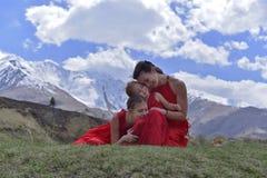 Een jonge vrouw met twee dochters in rood kleedt het rusten in de snow-capped bergen in de lente stock fotografie
