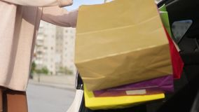 een jonge vrouw met zakken verheugt zich na het winkelen Een shopaholic blondevrouw overweegt haar aankopen in de boomstam van stock videobeelden