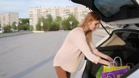 een jonge vrouw met zakken verheugt zich na het winkelen Een shopaholic blondevrouw overweegt haar aankopen in de boomstam van stock video