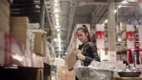 Een jonge vrouw neemt één doos uit andere, vindt wat zocht zij en glimlachen, zet het op een karretje stock videobeelden