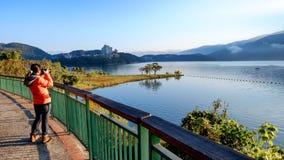 Een jonge vrouw neemt een foto van een mooi natuurlijk landschap bij het Meer van de Zonmaan, Taiwan royalty-vrije stock afbeeldingen