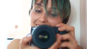 Een jonge vrouw neemt zich aan de camera door een spiegel stock footage