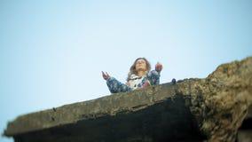 Een jonge vrouw oefent yoga dichtbij een oude uitstekende spoorwegbrug uit stock footage