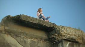 Een jonge vrouw oefent yoga dichtbij een oude uitstekende spoorwegbrug uit stock video