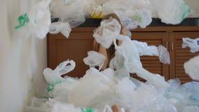 Een jonge vrouw is omvat met plastic zakken en door de hoeveelheid plastiek met afschuw vervuld die hij gebruikt Het concept van stock video