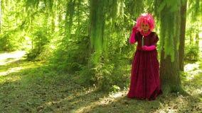 Een jonge vrouw onder het mom van een heks in een bos met een kaars is bezig geweest met magisch stock footage