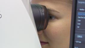Een jonge vrouw ondergaat een oftalmologisch onderzoek, controlerend de gezondheid van de ogen en visuele scherpte stock videobeelden