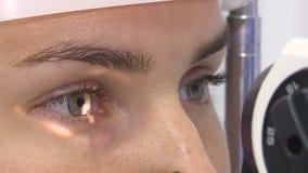 Een jonge vrouw ondergaat een oftalmologisch onderzoek, controlerend de gezondheid van de ogen en visuele scherpte stock footage