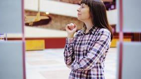 Een jonge vrouw onderzoekt de tentoonstelling in de galerij stock videobeelden