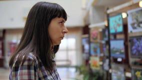 Een jonge vrouw onderzoekt de tentoonstelling in de galerij stock video