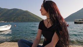 Een jonge vrouw op de achtergrond van een overzeese baai en een bergketting stock videobeelden