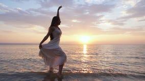 Een jonge vrouw op het strand die met water bespatten en stelt tevreden stock footage