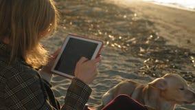 Een jonge vrouw op het strand door de rivier gebruikt een computertablet en voedt een bruine lobrodorhond o stock footage