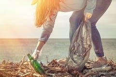 Een jonge vrouw op een schoonmaak die van het kustgebied, huisvuil verzamelen Overzees en hemel op de achtergrond Aardedag en eco stock afbeelding