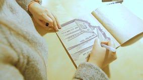 Een jonge vrouw opent de teller en begint in het album te trekken stock video