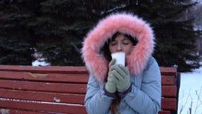 Een jonge vrouw probeert om met een hete drank op een koude de winterdag te verwarmen stock videobeelden