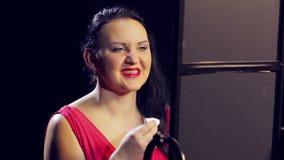 Een jonge vrouw in een rode kleding met rode lippenstift verwijdert bovenmatige make-up met een katoenen stootkussen stock video