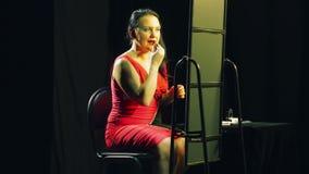 Een jonge vrouw in een rode kleding voor een spiegel past heldere rode lippenstift op haar lippen toe stock videobeelden
