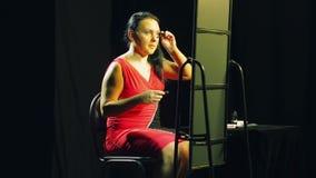 Een jonge vrouw in een rode kleding voor een spiegel schildert haar wimpers met zwarte mascara stock video