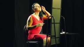 Een jonge vrouw in een rode kleding voor een spiegel schildert haar wimpers met zwarte mascara stock footage