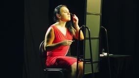 Een jonge vrouw in een rode kleding voor een spiegel schildert haar wimpers met zwarte mascara stock videobeelden