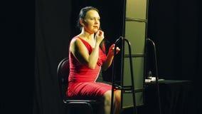 Een jonge vrouw in een rode kleding voor een spiegel zet een rode contour op haar lippen stock video